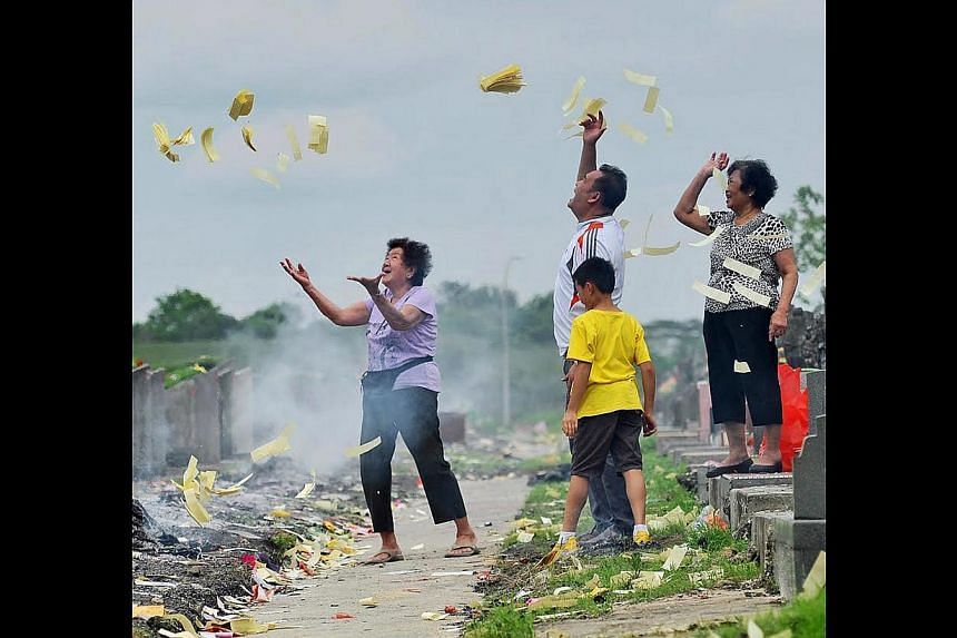A family observing rituals during the Qingming Festival at Choa Chu Kang Chinese Cemetery. -- ST PHOTO: MATTHIAS HO