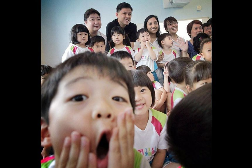 Children gather for a photo with Minister for Social and Family Development Chan Chun Sing at MY World @ Simei childcare centre. -- ST PHOTO: NEO XIAOBIN