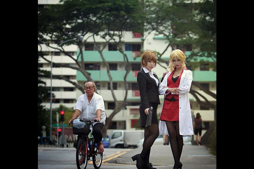 A cyclist seems indifferent to a photoshoot for Taiwanese cosplayers dressed as characters from Psycho Pass. -- ST PHOTO: NEO XIAOBIN