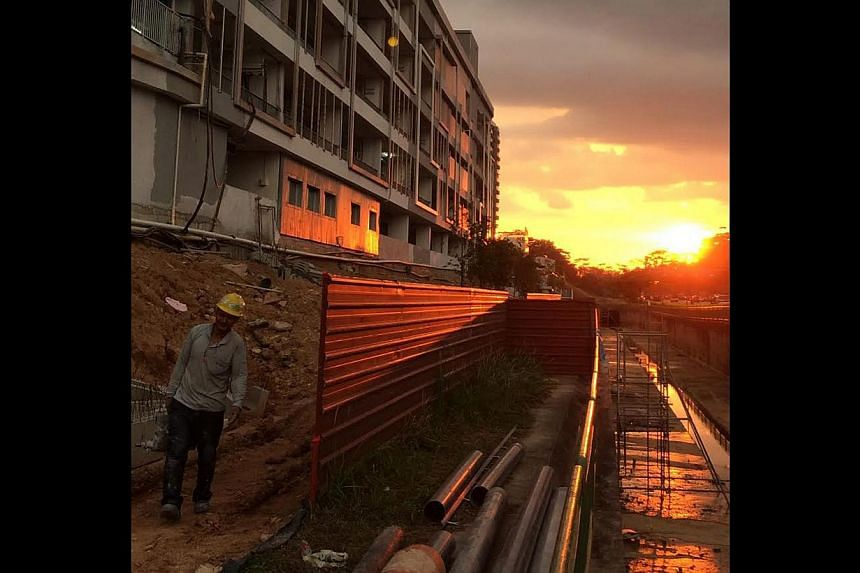 The setting sun marks the end of the shift for a worker leaving a construction site in Bukit Panjang. -- ST PHOTO: NG SOR LUAN