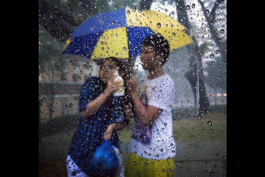 Singing in the rain? Not quite, as a couple take shelter under an umbrella during a heavy downpour at Lengkok Bahru. -- ST PHOTO: NG SOR LUAN