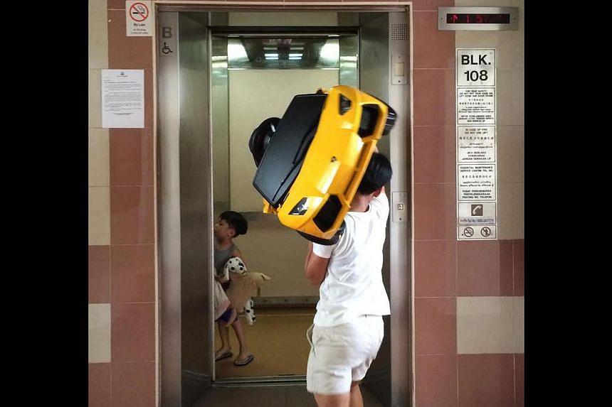 """You carry, I'll hold the lift."" A domestic helper lifting a boy's toy Lamborghini Aventador into a lift. -- ST PHOTO: NG SOR LUAN"