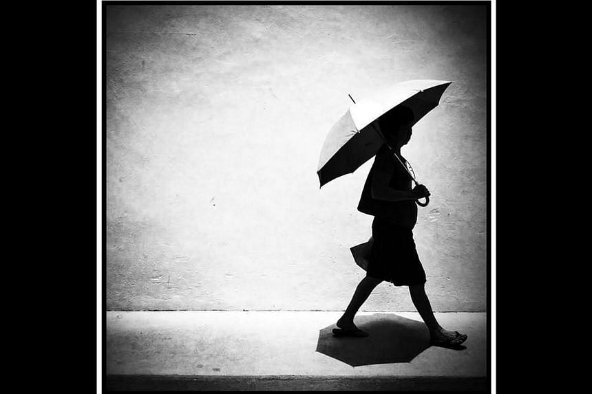 An umbrella provides shade from the blazing midday sun for a pedestrian on Sunset Way. -- ST PHOTO: MALCOLM McLEOD