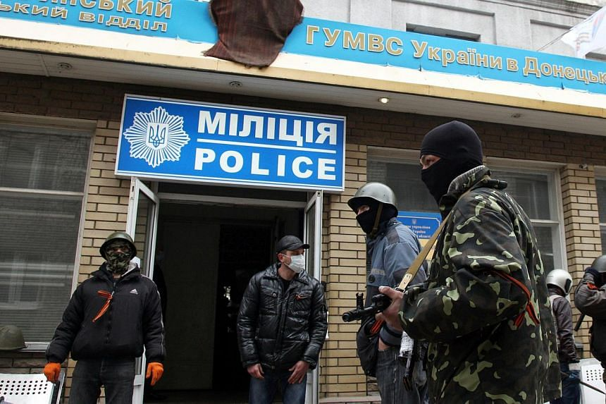 Armed pro-Russian activists guard a police station in the eastern Ukrainian city of Slaviansk after it was seized by a few dozen gunmen on April 12, 2014. -- PHOTO: AFP