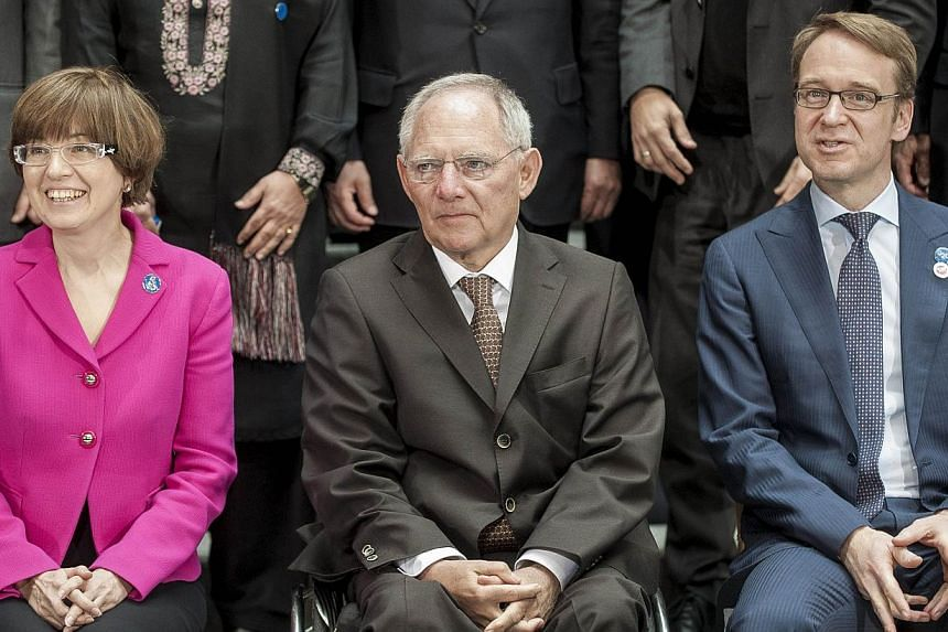 Russian Monetary policy chief Ksenia Yudaeva, German Finance Minister Wolfgang Schaeuble and Jens Weidmann, president of Germany's Bundesbank, pose for the International Monetary and Financial Committee (IMFC) family photo at the IMF/World Bank Sprin
