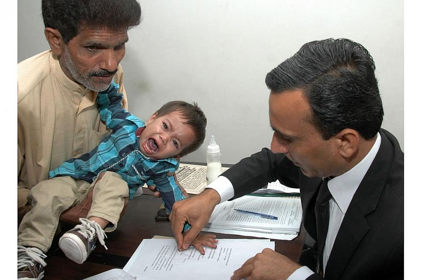 A Pakistani lawyer taking a thumb impression from nine-month-old baby Musa Khanon a bail bond in Lahore, on April 3, 2014. A Pakistani judge threw out charges of attempted murder against Musa on Saturday, April 12, 2014, lawyers said, in a case
