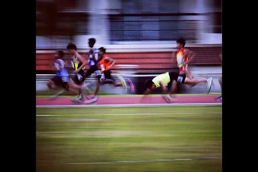 A runner takes a tumble during a 1500m heat at the Schools' National Track and Field Championships at Choa Chu Kang Stadium on April 8, 2014. -- ST PHOTO: MARK CHEONG