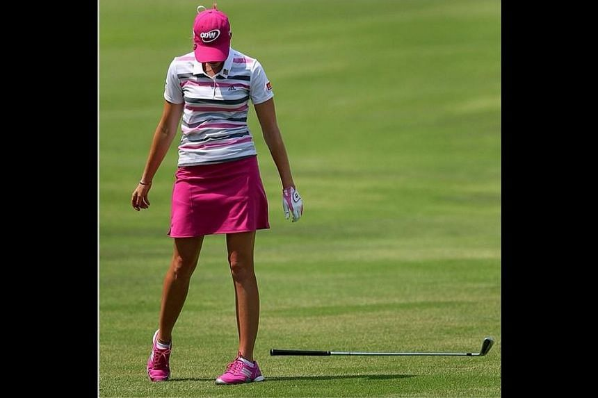 US golfer Paula Creamer drops her club after a poor shot during the final round of the HSBC Women's Champions. She went on to sink a 23m eagle on the second play-off hole against Azahara Munoz to win her first LPGA title since the 2010 US Women's Ope