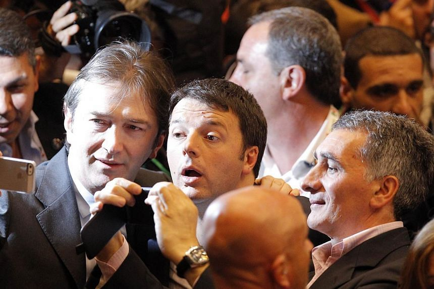 Prime Ministre Matteo Renzi (centre) poses for a selfie during a campaign meeting of the Democratic Party (PD) on April 12, 2014, at the Palaolimpico in Turin ahead of the European elections. Italy's new prime minister on Saturday blasted what he cal