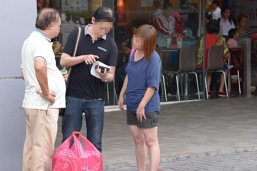An NEA officer (centre) books an offender (right) for littering during the agency's latest enforcement blitz, conducted islandwide at more than 30 littering hotspots. -- ST PHOTO: LIM SIN THAI