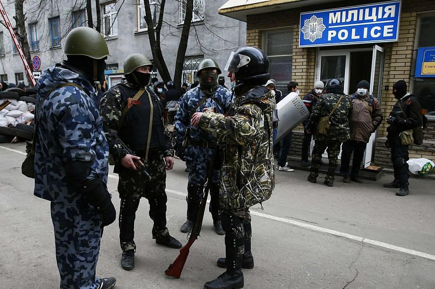 Armed men stand in front of police headquarters in Slaviansk, on April 12, 2014. Kalashnikov-wielding gunmen on Saturday seized a police station and a security building in Ukraine's restive eastern industrial heartland amid spreading protests to pres