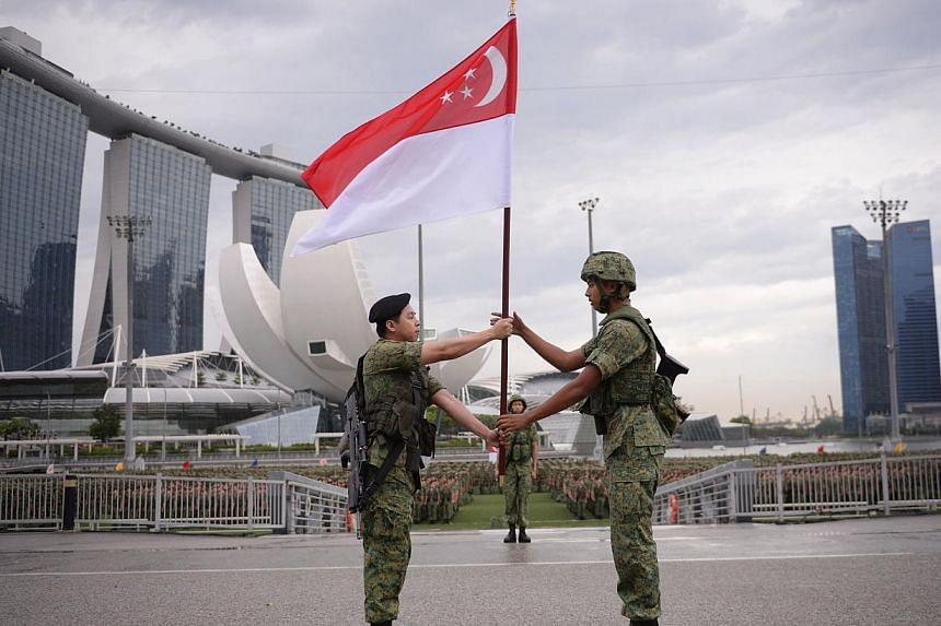 NSman Corporal Lee Hong Cheng (left) handing over the national flag to his nephew, graduating recruit Marcus Chin, at the Singapore Armed Forces' first integrated military parade on Saturday morning. -- ST PHOTO: MARK CHEONG