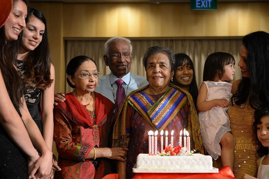 Left: Mrs Mangalesvary Ambiavagar (centre), the former principal of Raffles Girls' Primary School, standing before her 100th-birthday cake at the Singapore Swimming Club yesterday. With her are (from left) great-granddaughters Grace Nathan, 20, and T