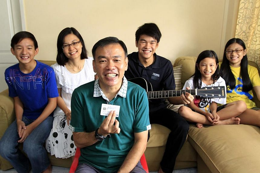 Social worker Lim Swee Hock charges at least $400 to $500 a month to his NTUC Plus! Visa card. With him are (from far left) 13-year-old son Joash, his wife Connie, 16-year-old son Matthew and daughters Anna, 10, and Sophia, 15. -- ST PHOTO: CHEW SENG