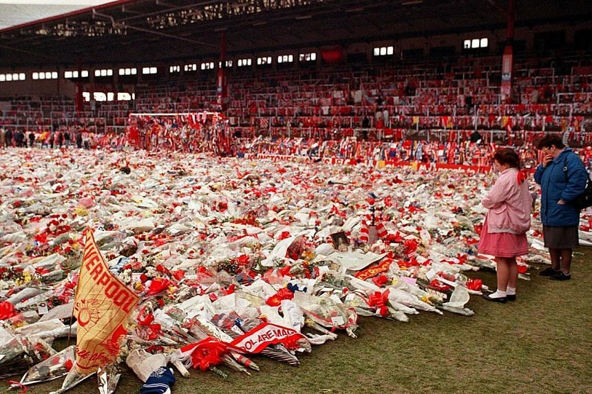 In file pictures taken in April 1989, thousands of bunches of flowers, wreaths and tributes lie on the pitch at Anfield (above) in memory of the 96 football fans who died in the Hillsborough disaster, which happened because of a crush on the terraces