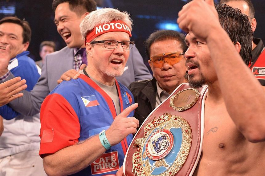Manny Pacquiao of Philippines (right) and trainer Freddie Roach (left) celebrate victory over Timothy Bradley of the US following their WBO World Welterweight Championship title match at the MGM Grand Arena in Las Vegas, Nevada, on April 12, 2014. --
