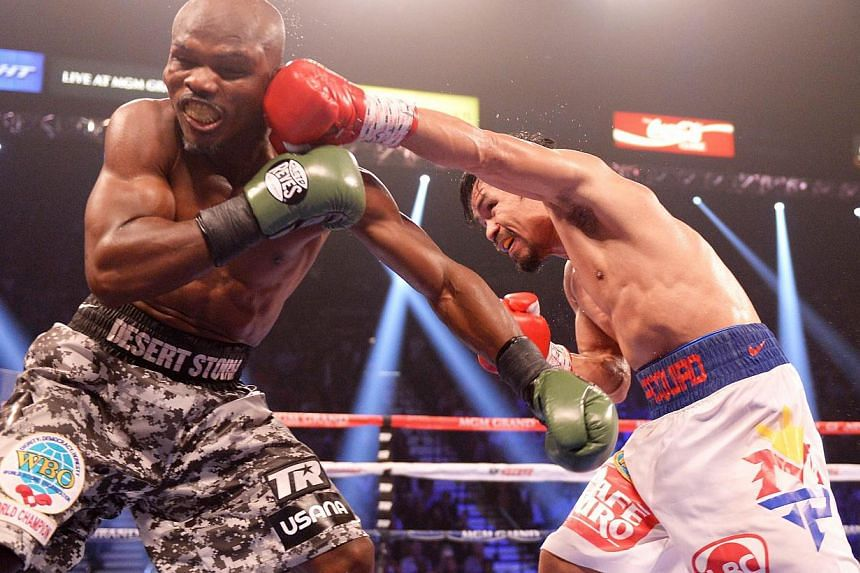 Timothy Bradley of the United States is on the receiving end against Manny Pacquiao of Philippines (right) during their WBO World Welterweight Championship title match at the MGM Grand Arena in Las Vegas, Nevada, on April 12, 2014. -- PHOTO: AFP&nbsp