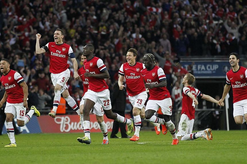 The Arsenal team run to celebrate after Arsenal's Spanish midfielder Santi Cazorla scored his penalty bringing Arsernal to win 4-2 on penalties during the English FA Cup Semi-final match between Wigan Athletic and Arsenal at Wembley Stadium in London