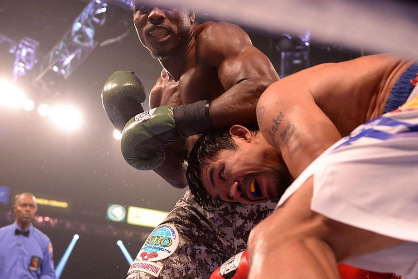 Timothy Bradley of the United States (left) goes on the offensive against Manny Pacquiao of Philippines during their WBO World Welterweight Championship title match at the MGM Grand Arena in Las Vegas, Nevada, on April 12, 2014. -- PHOTO: AFP