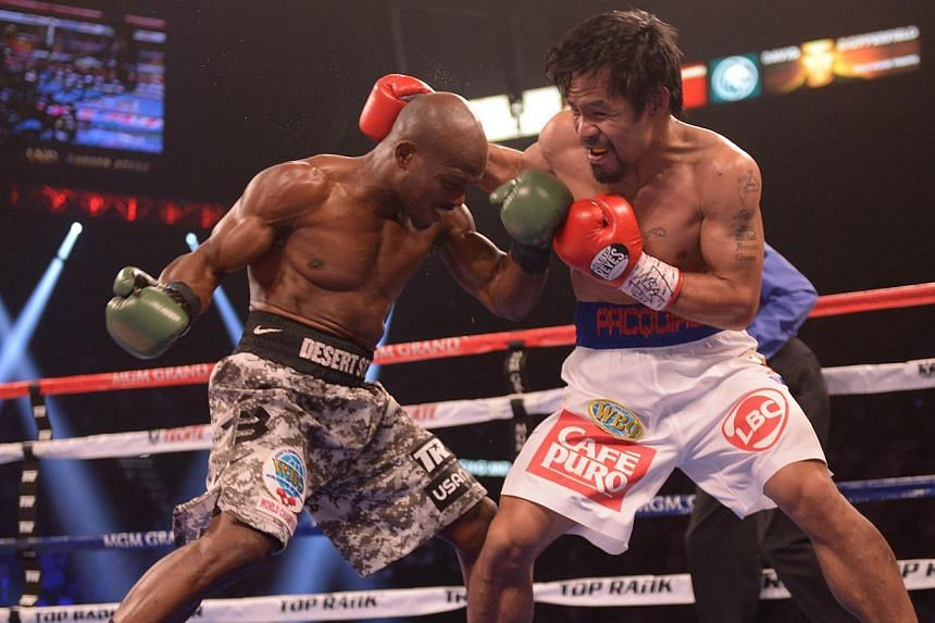Timothy Bradley of the United States (left) exchanges blows with Manny Pacquiao of Philippines during their WBO World Welterweight Championship title match at the MGM Grand Arena in Las Vegas, Nevada, on April 12, 2014. -- PHOTO: AFP