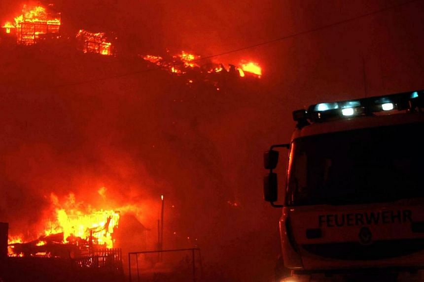 A firefighter truck stands near houses on fire in Valparaiso, 110km west of Santiago, Chile on April 12, 2014. -- PHOTO: AFP