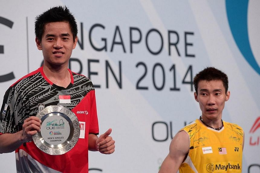 Winner Simon Santoso (left) of Indonesia and runner-up Lee Chong Wei (right) of Malaysia pose for photographs during the OUE Singapore Open badminton tournament men's final on April 13, 2014. -- PHOTO: AFP