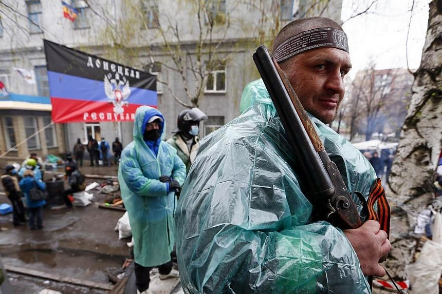 A pro-Russian armed man stands guard at a barricade near the police headquarters in Slaviansk on April 13, 2014.Ukraine's interior minister said on Sunday that both sides had suffered casualties during a raid launched by Ukrainian special force