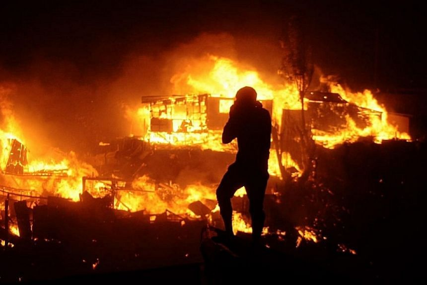 A firefighter stares at burning houses during a fire in Valparaiso, 110km west of Santiago, Chile on April 12, 2014. -- PHOTO: AFP