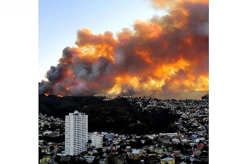 View of houses in flames during a fire in Valparaiso, 110km west of Santiago, Chile, on April 12, 2014.Four people have died in a huge fire that on Sunday, April 13, 2014, was consuming the outskirts of Chile's port city of Valparaiso and was a