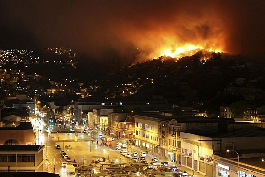 A forest fire burns in Valparaiso city, northwest of Santiagoon on April 12, 2014. -- PHOTO: REUTERS