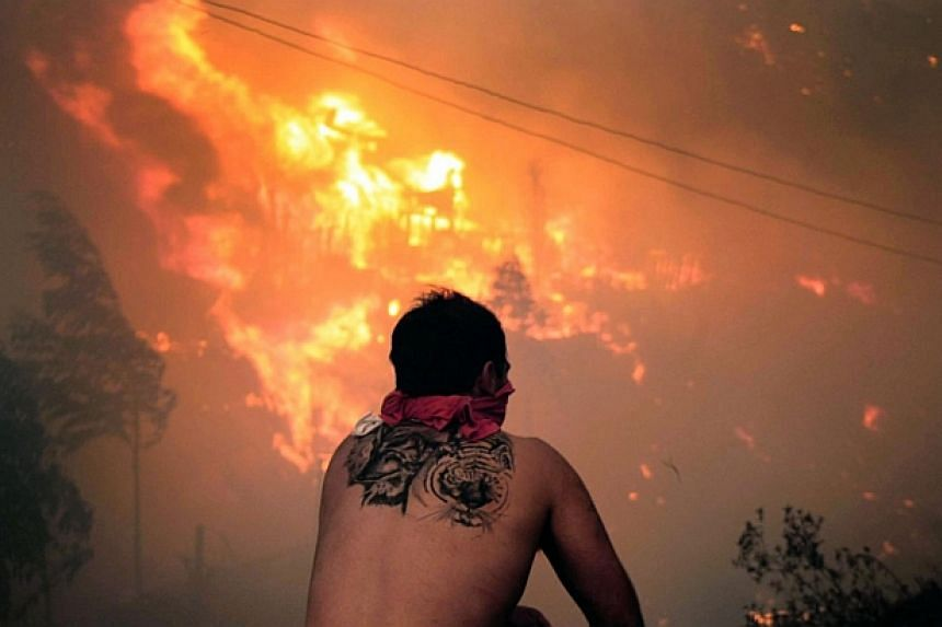 A local stares at houses in flames during a fire in Valparaiso, 110km west of Santiago, Chile on April 12, 2014. -- PHOTO: AFP