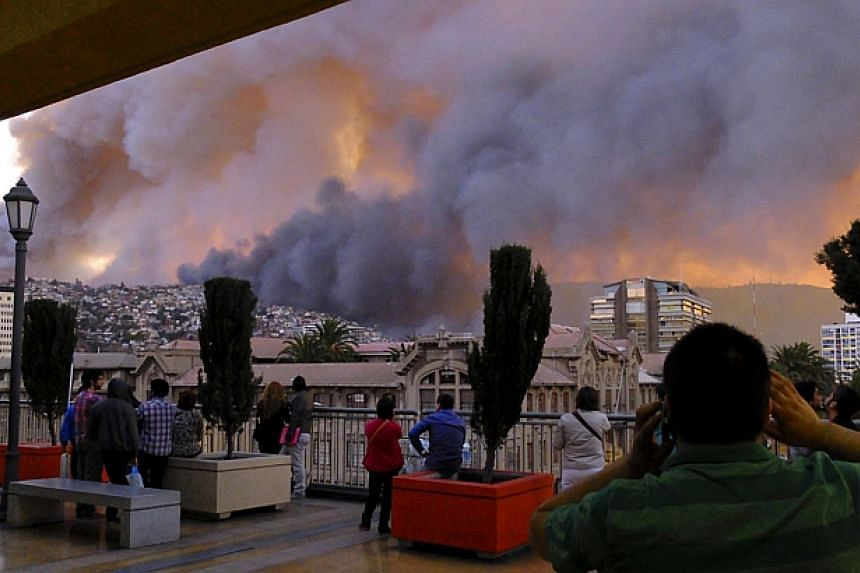 People look at smoke from a forest fire in Valparaiso city, northwest of Santiago on April 12, 2014. -- PHOTO: REUTERS