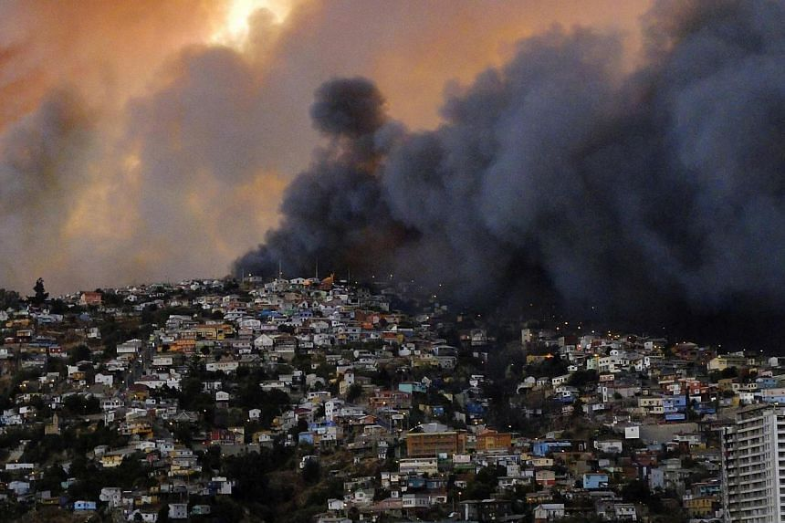 Smoke from a forest fire is seen in Valparaiso city, northwest of Santiago on April 12, 2014. -- PHOTO: REUTERS