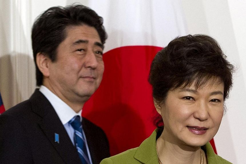 South Korean President Park Geun-hye and Japanese Prime Minister Shinzo Abe arrive for a trilateral meeting with the US presidentat the US ambassador's residence in The Hague on March 25, 2014, after they attended the Nuclear Security Summit (NSS).&n