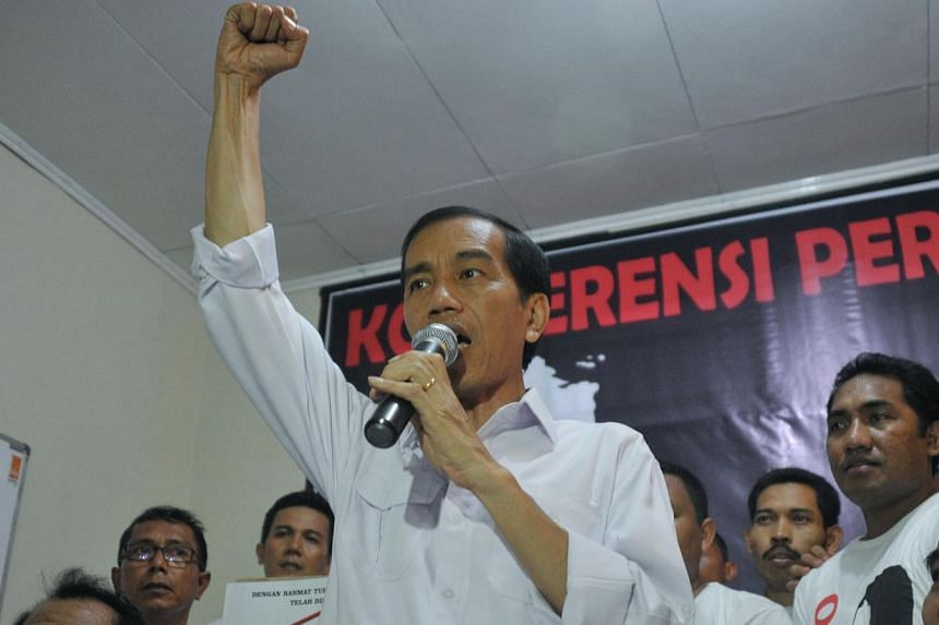 Popular presidential candidate of main opposition party Indonesian Democratic Party of Struggle (PDI-P) and Jakarta Governor Joko Widodo (centre) gestures during a press conference in Jakarta on April 11, 2014.A small Indonesian political party