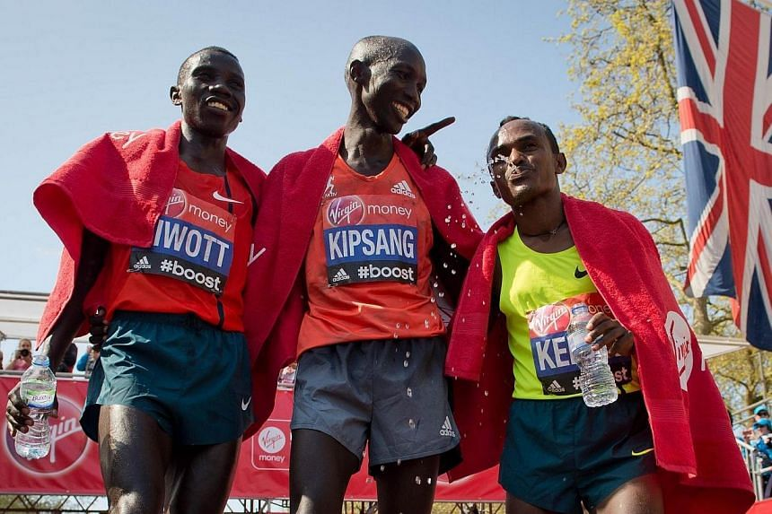 Second place Stanley Biwott (left), first place Wilson Kipsang of Kenya (centre) and third place Tsegaye Kebede of Ethiopia (right) pose for photographs after completing the men's race in the 2014 London Marathon on The Mall in central London on Sund