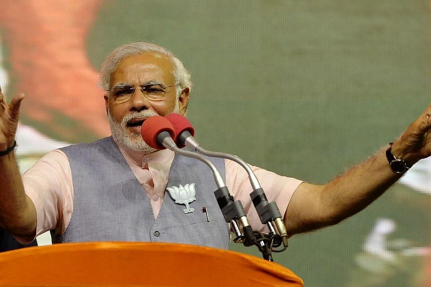 """Chief Minister of the western Indian state of Gujarat and Bharatiya Janata Party (BJP) Prime Ministerial andidate Narendra Modi gestures as he addresses supporters during the """"Bharat Vijay"""" rally held on the outskirts of Bangalore on April 8, 2"""