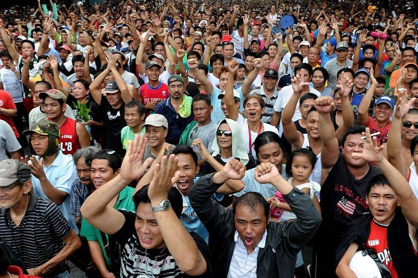 Thousands of Filipinos gathered at a public park cheer as the country's boxing hero, Manny Pacquiao is declared the winner over Timothy Bradley of the US in a live broadcast of the fight from Las Vegas, in Manila on Sunday, April 13, 2014.The P