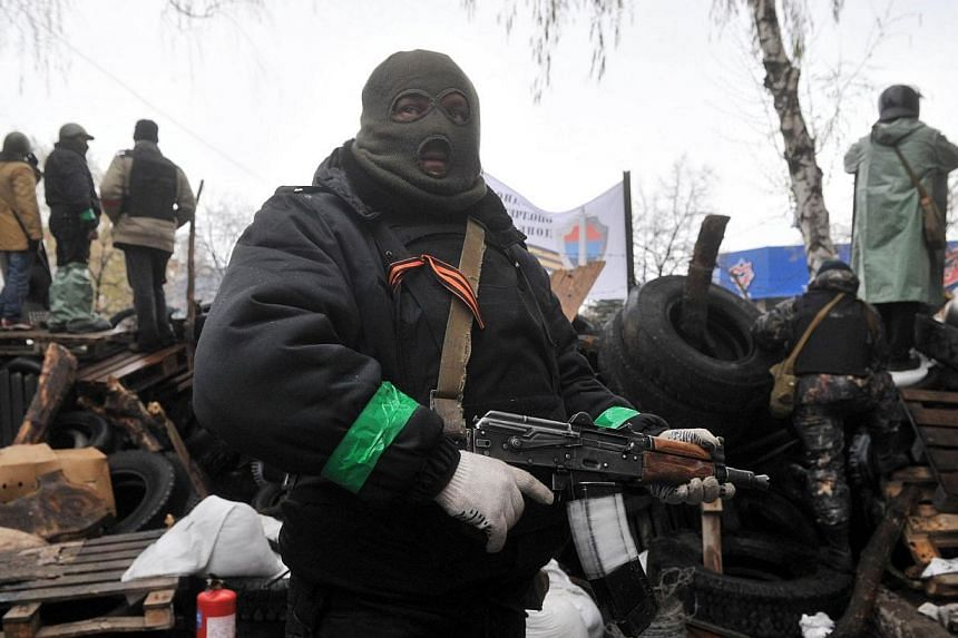 """Pro-Russia protesters guard a barricade outside a regional police building seized by armed separatists in Slavyansk on Sunday, April 13, 2014.Attacks on the police and security service buildings in eastern Ukraine by pro-Russian gunmen bore """"te"""