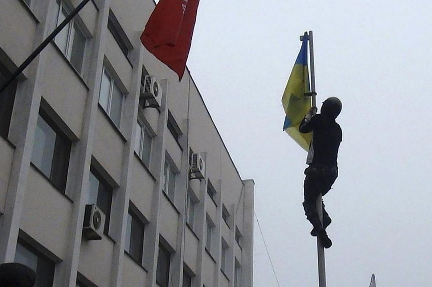 A man climbs up a post to remove a Ukrainian flag as protesters hold a rally outside the mayor's office in Mariupol on Sunday, April 13, 2014. Separatist protesters on Sunday seized control of the mayor's office in the town of Mariupol, eastern