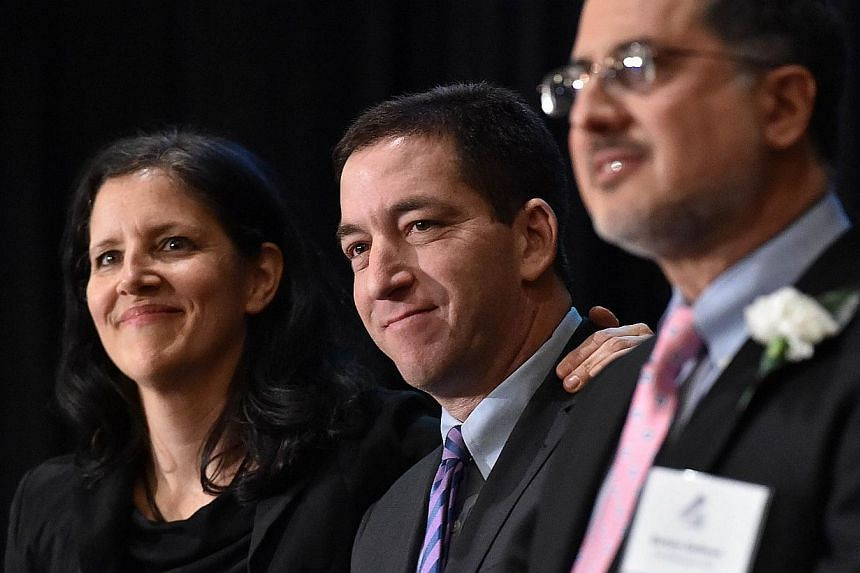 Laura Poitras (left) and Glenn Greenwald (centre) in the United States for the first time since documents were disclosed to them by former intelligence analyst Edward Snowden, accept Long Island University's George Polk Award for National Security Re