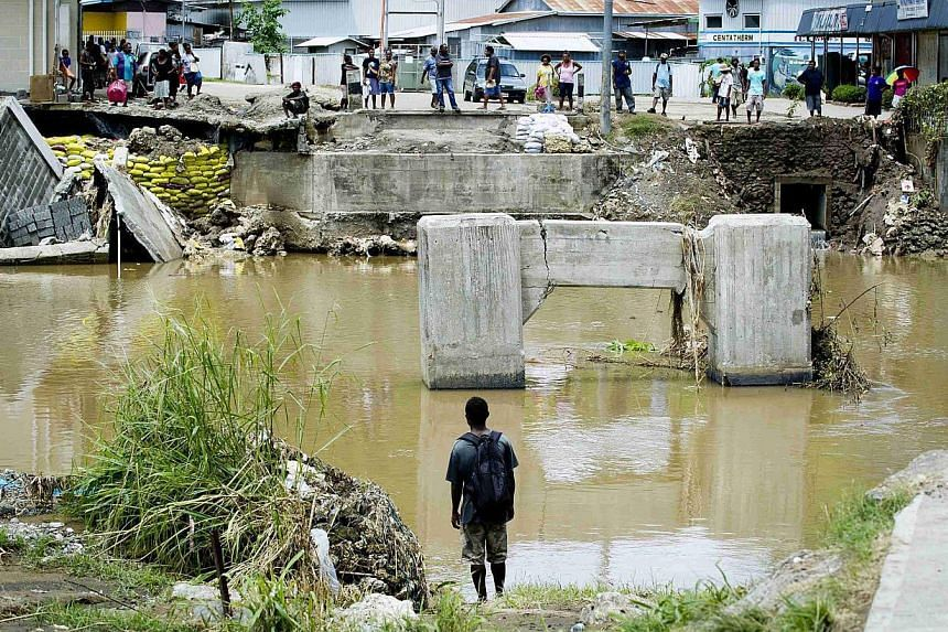 Locals look at a bridge that was destroyed as a result of severe flooding near the capital Honiara in the Solomon Islands in this handout picture released by the Australian Defence Force on April 9, 2014. -- FILE PHOTO: REUTERS