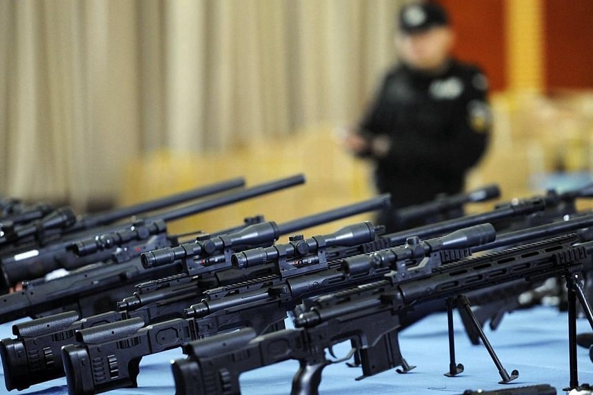 A policeman stands near confiscated replica guns on display at a police station in Guiyang, Guizhou province March 6, 2014. -- PHOTO: REUTERS