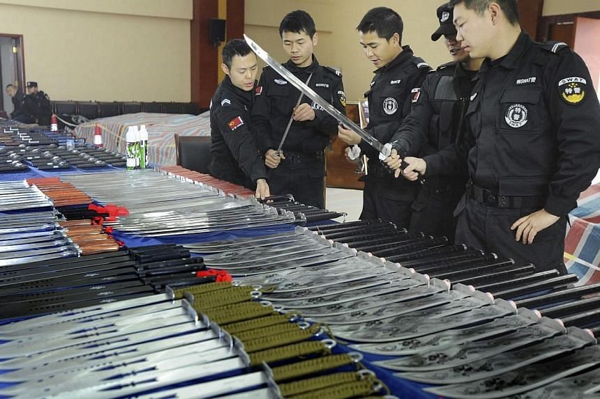 Policemen look at confiscated knives on display at a police station in Guiyang, Guizhou province March 6, 2014. -- PHOTO: REUTERS