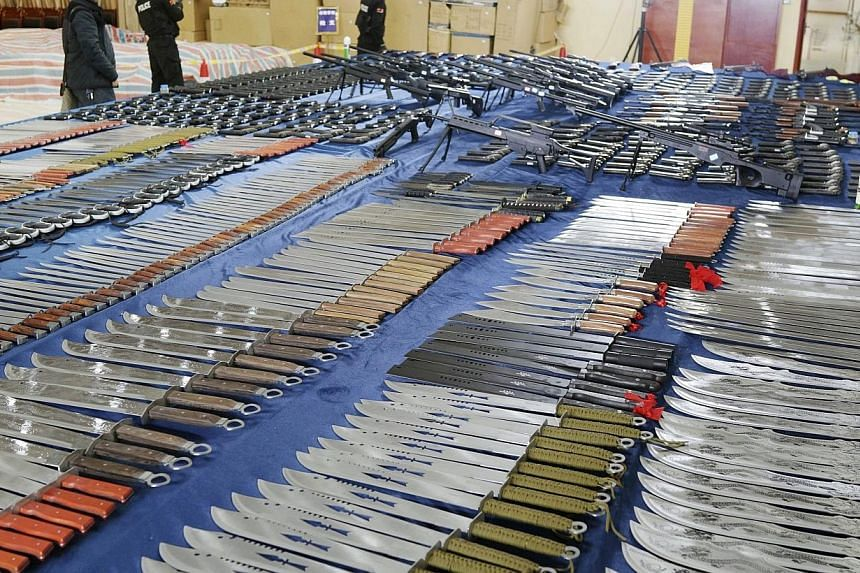 Policemen stand next to confiscated knives and replica guns on display at a police station in Guiyang, Guizhou province March 6, 2014. -- PHOTO: REUTERS