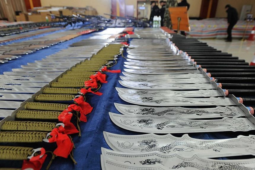 This picture taken on March 6, 2014 shows knives and guns confiscated by police in Guiyang, southwest China's Guizhou province. -- PHOTO: AFP