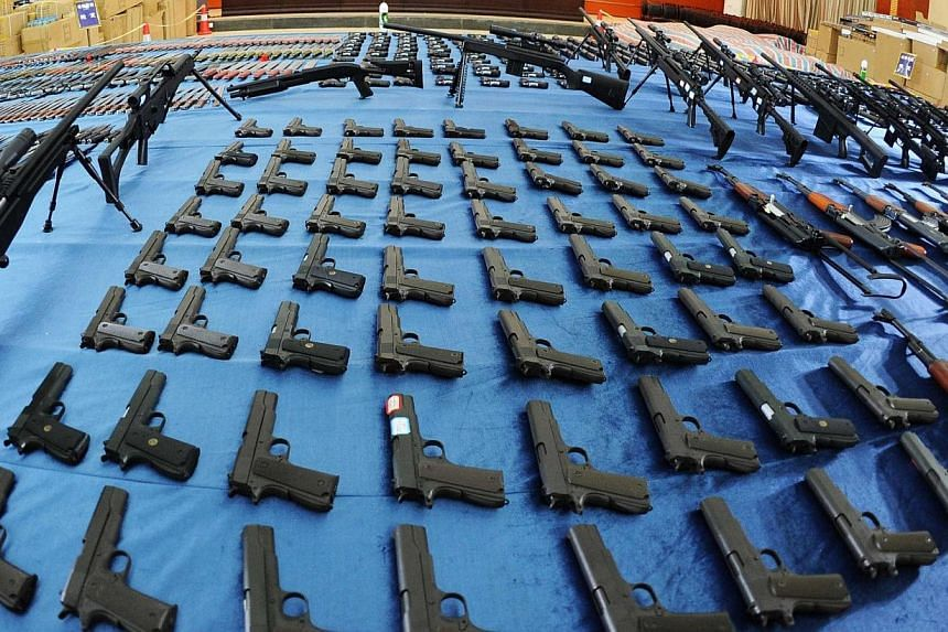 This picture taken on March 6, 2014 shows guns and knives confiscated by police in Guiyang, south-west China's Guizhou province.  -- PHOTO: AFP