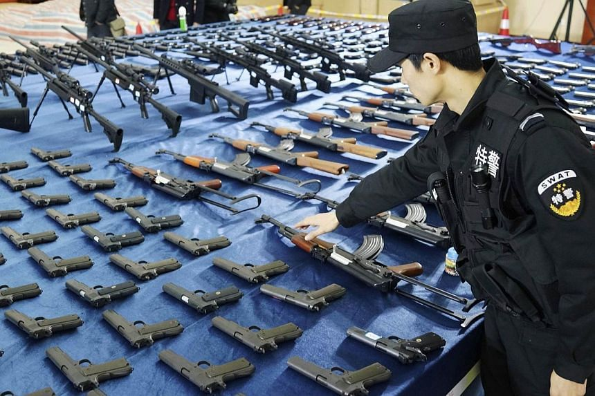 A policeman checks on confiscated illegal replica guns in Guiyang, Guizhou province, March 6, 2014. A huge cache of weapons, including 15,000 guns and 120,000 knives, was seized from an illegal arms ring and 15 suspects detained, state media reported