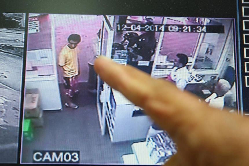 An official pointing at the closed-circuit television image of a Singaporean man who set himself ablaze at a petrol kiosk in Johor Baru on April 12, 2014. The 42-year-old Singaporean who set himself on fire near a Johor Baru petrol kiosk on Satu