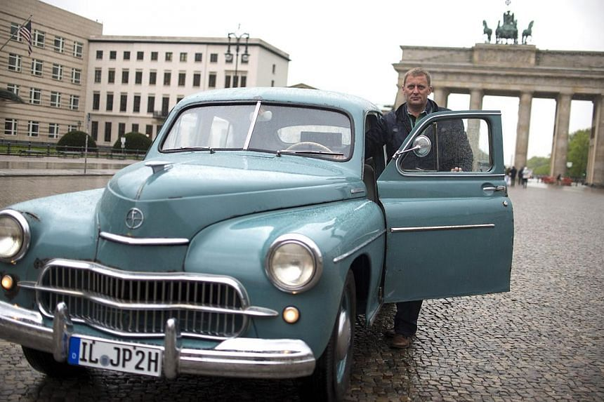 Marek Schramm poses next to his old-timer, a former car of Pope Jean Paul II in front of the Brandenburg Gate on the April 14, 2014 in Berlin, prior to his trip to Rome for Pope's canonization.A German vintage car enthusiast set off on Monday i